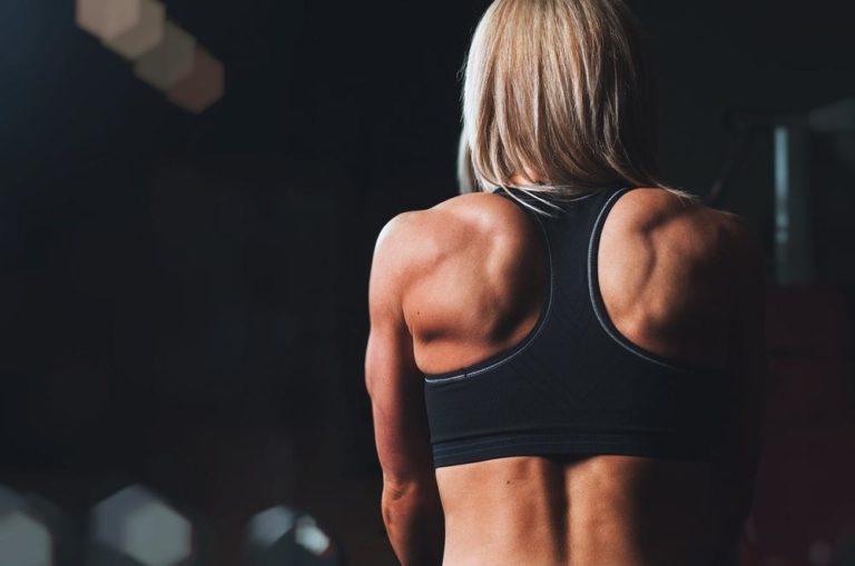 una donna idnossa un correttore posturale alle spalle